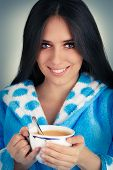 Young Woman in Bathrobe Holding a Big Cup of Coffee