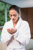 Beautiful young woman in bathrobe holding flowers in spa