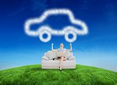 Cheering beautiful businesswoman sitting on couch against green hill under blue sky