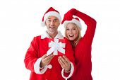Festive couple smiling and holding gift on white background