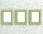 Three frames on white brick wall