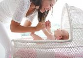 Smiling Woman Holding Baby In Cot