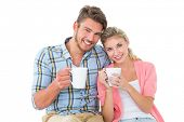 Attractive young couple sitting holding mugs on white background