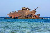 Rusting Metal Shipwreck On A Coral Reef