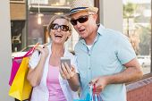 Happy mature couple looking at smartphone together in the city on a sunny day