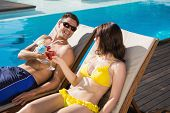 Smiling young couple toasting drinks by swimming pool