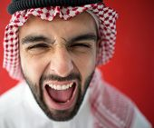 Arabic young businessman posing on red wall yelling celebrating