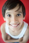 Adorable little happy boy looking at camera on red background
