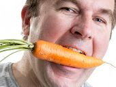 Man holding a fresh carrot in his mouth