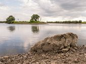 Large Rock By Quiet River In Doesburg, Holland