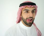 Arabic young businessman posing on red wall