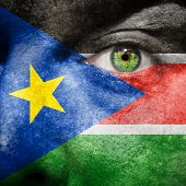 picture of sudan  - Flag painted on face with green eye to show South Sudan support - JPG