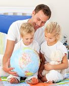 Adorable Children And Their Father Looking At A Terrestrial Globe