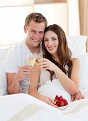 Enamoured Couple Drinking Champagne With Strawberries Lying In Bed