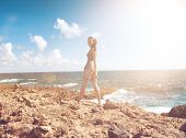 Young woman enjoying the seaside standing on a rocky seashore in the flare of the hot tropical summe