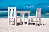 Idyllic outdoor dining on a tropical beach in Aruba with fresh white painted wooden table and chairs on clean white sand alongside a calm azure blue ocean in hot summer sunshine