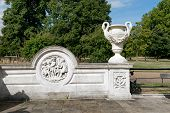 pic of swag  - Ornamental urn with two elegant swans heads holding a floral swag or wreath and relief caving in a circular plaque on a white wall overlooking a formal garden - JPG