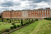 Picturesque view of Hampton Court Palace, London, UK looking across the manicured lawns at the state