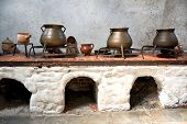 Display of old earthenware and iron cooking pots on an old kitchen range with arched stone ovens below in an ancient castle or country house
