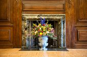 Flower arrangement of colorful summer blooms in a blue and white pottery urn in a historical marble
