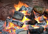 Glowing coals in a wood fire with fiery orange flames in a brick hearth or fireplace with a wrought