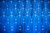 HAMPTON COURT, UK - AUGUST 03, 2014 - Historical blue drapery textile patterned with the royal crown