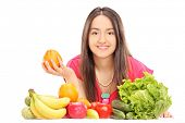 Woman posing behind fruits and vegetables isolated on white background