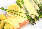 Baked salmon with asparagus, lemon, potatoes and sauce hollandaise on a plate