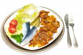 Two herring with fried potatoes and cream-dip on a plate with tomato- and cucumber decoration