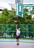 Thai Student Is Doing A Layup Shoot In Public Basketball Court.