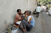 KOLKATA, INDIA - NOVEMBER 26: Street barber shaving a man using an open razor blade on a street in Kolkata, West Bengal, India on Nov 26, 2012