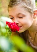 Portrait of a cute little girl smelling rose, outdoor shoot