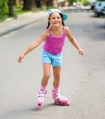 Happy little girl is skating on rollers, outdoor shoot