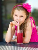 Little girl is drinking cherry juice using straw while sitting on terrace