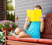 Cute little girl is reading a book while sitting on bench