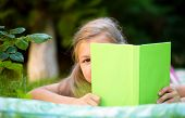 Little girl is hiding behind book while laying on green grass