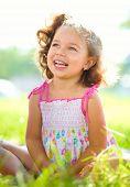 Portrait of a cute little girl sitting on green grass, outdoor shoot