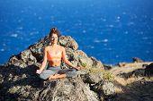 Woman meditating practicing yoga outdoors