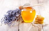 stock photo of honeycomb  - jar of honey with honeycomb and lavander flowers on wooden table - JPG
