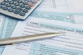 stock photo of irs  - Filling in US income tax return IRS 1040 forms - JPG