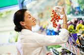 woman choosing tomato during shopping at fruit vegetable supermarket