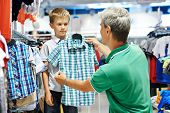 man father choosing shirt with son boy during shopping at garments shop