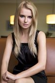 attractive young adult sensuality blond woman in black dress sitting on the couch