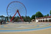 KHARKOV, UKRAINE - JUNE 10, 2014: People resting in front of the Ferris wheel in the Central park named after M. Gorky. The Ferris wheel is 55 m tall, and is the largest in Ukraine