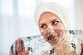 Islamic girl in white posing with black lace in front of face