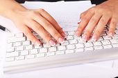 Female hands typing on keyboard, close-up, on light background