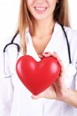 Young beautiful doctor holding red heart, close-up