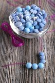Beads in small glass bowl and on lace on wooden background