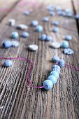 Beads on lace on wooden background
