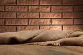 Wooden table with cloth on wall background